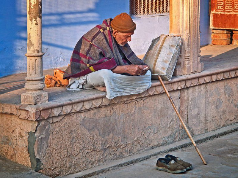 An old man sits counting his money on the streets of Jodhpur, India.