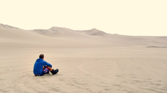 Scott sits alone in the sand