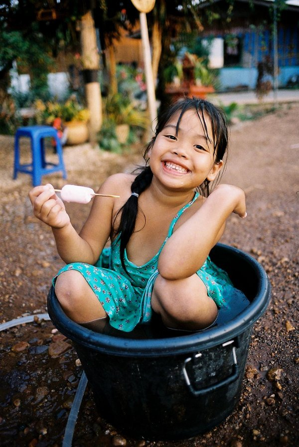 Thai girl sitting in a bucket of water