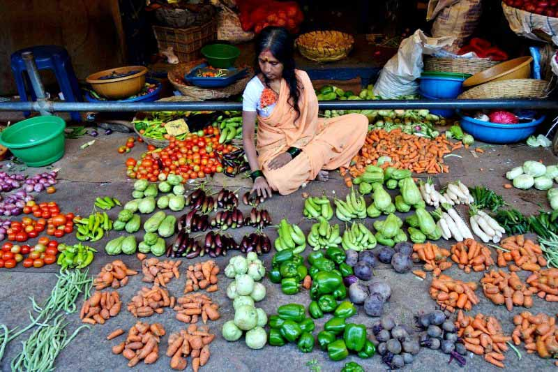 A lady selling fresh vegetables