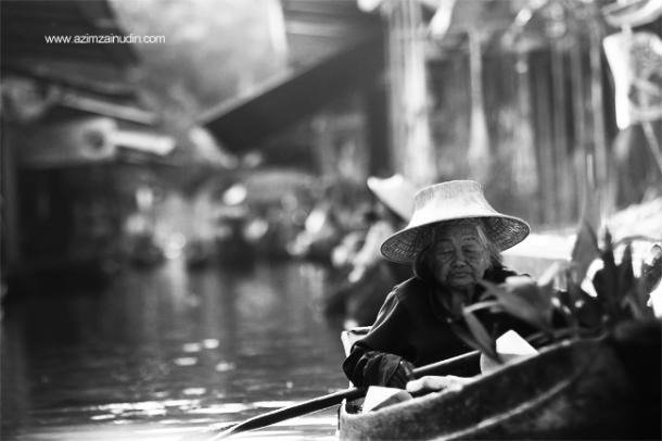 An old woman selling fruits at the Damnoen Saduk Floating Market in Thailand