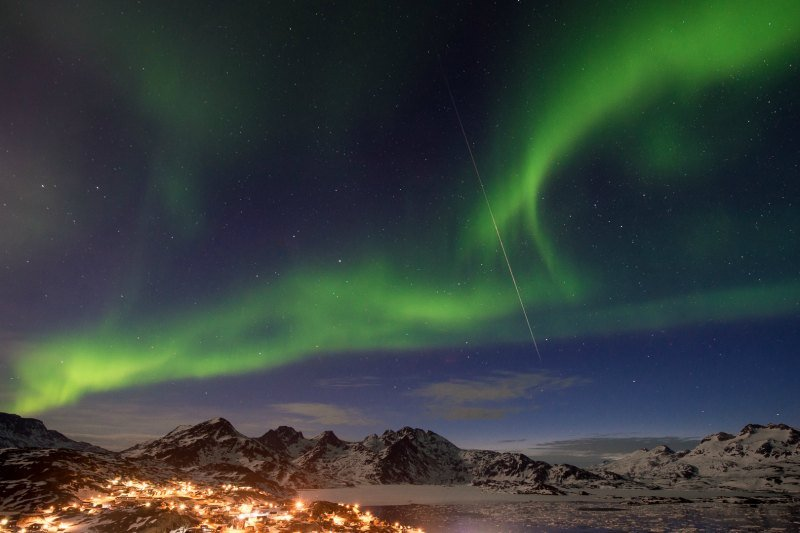 Northern lights with a shooting star over the town of Tasiilaq in East Greenland