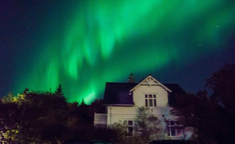 A house is illuminated by the aurora